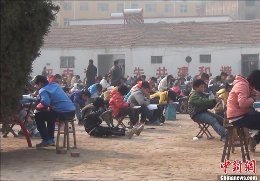现拥有900余名学生的城镇中学教学设备极为简陋。城镇中学工作人员向记者介绍称,由于该校处于城乡结合部,现在有600多名学生需要住校,而只能拥挤在两层小楼内,该楼的另一部分用于教师办公使用。记者在一楼的学生宿舍看到,大约50平米的房间拥挤排列着30张双层床铺,至少住着50余位学生。紧邻台前县政府1公里之遥的城镇中学,由于教室不充裕,学生在室外空地上考试。董飞 摄