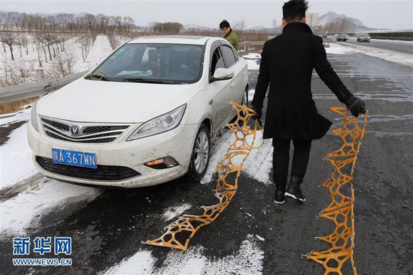 2月13日,在京哈高速公路辽宁葫芦岛段,一名司机准备为车辆安装防滑链.