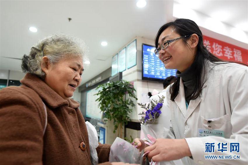 3月8日,重庆市人民医院的医护人员在医院向一名妇女送上鲜花,表达节日