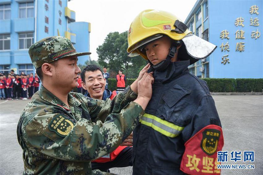 11月7日,小学生在志愿者与消防战士的帮助下穿戴防护服.