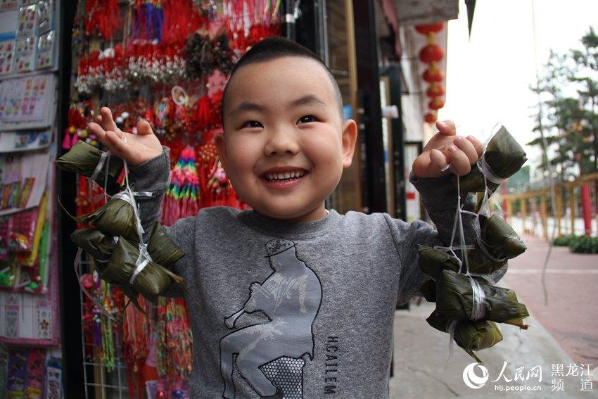 一名小朋友手提着刚买的粽子。
