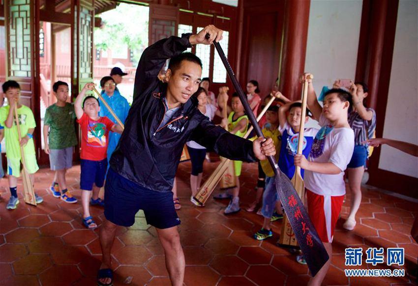 6月18日,福州大学龙舟队教练吴杰忠在教小学生正确划桨姿势。