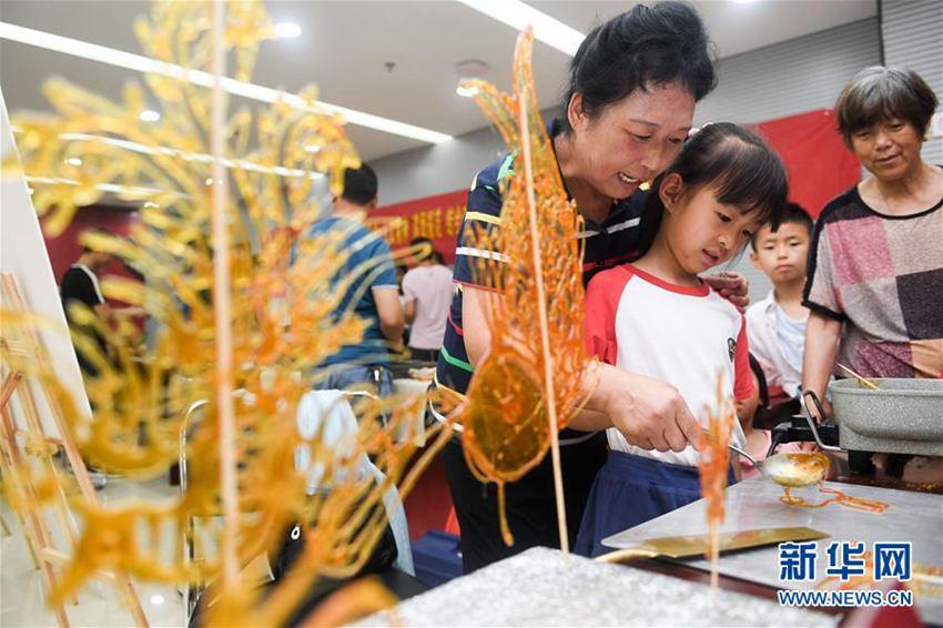 6月20日,在合肥市万年埠街道云华社区活动中心,非遗传承人张云萍(左)在教小朋友进行糖画创作。