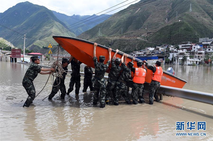7月15日,在舟曲县南峪乡,武警甘南支队战士在搬运冲锋舟。