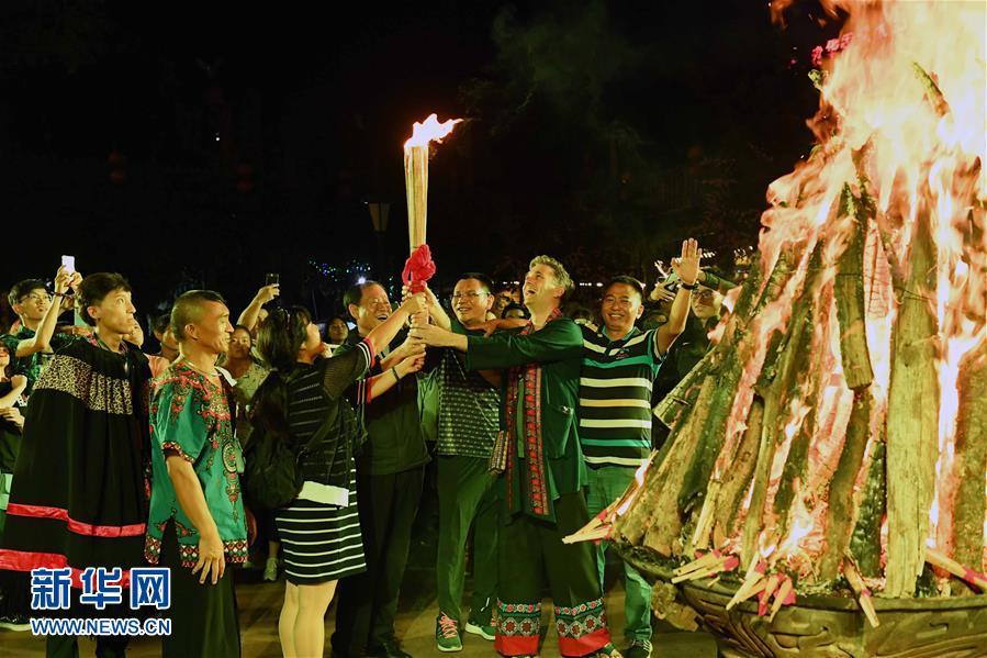 8月5日,游客在云南楚雄彝人古镇点燃火把。