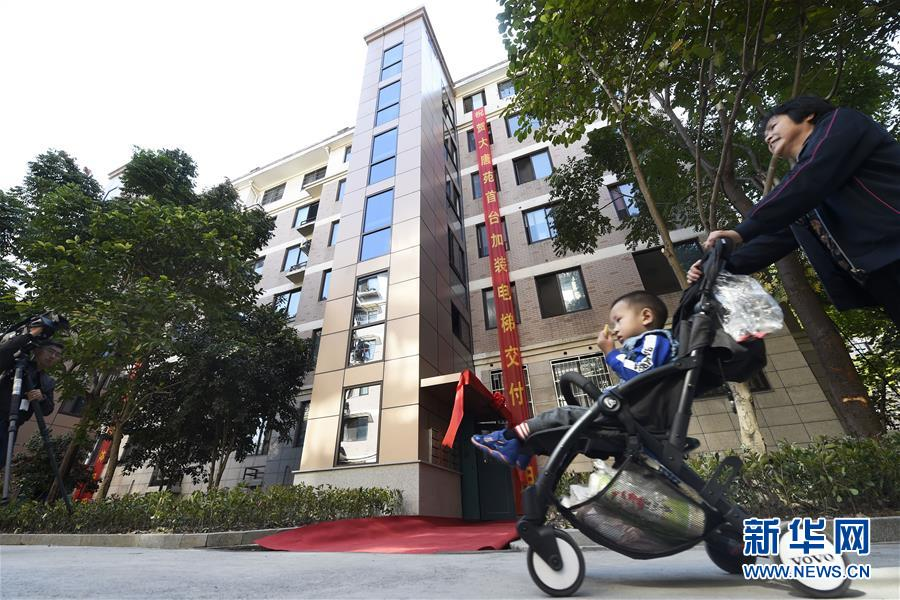 10月11日,大唐苑小区居民从加装了电梯的单元门前走过。