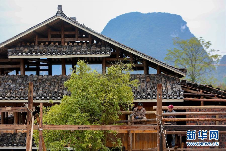 1月15日,工人在广西融水苗族自治县融水镇梦呜苗寨建设房屋。