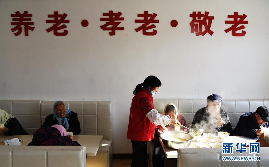 1月15日,村里的志愿者为就餐的老人分菜。